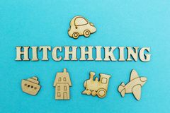 The word `hitchhiking` and the figure of the car on a blue background from above, plane, train, ship, hotel - from below stock image