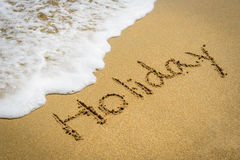 Word holiday on the beach sand Royalty Free Stock Images