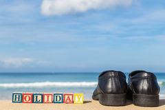 Word HOLIDAY in colorful alphabet blocks andblack shoe on tropic Royalty Free Stock Photography