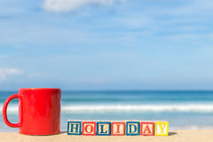 Word HOLIDAY in colorful alphabet blocks and coffee cup on tropi Stock Images