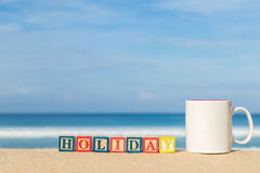 Word HOLIDAY in colorful alphabet blocks and coffee cup on tropi Royalty Free Stock Photo