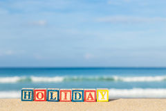 Word HOLIDAY in colorful alphabet blocks on tropical beach Royalty Free Stock Photography