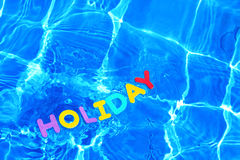 Word HOLIDAY floating in a swimming pool Stock Images