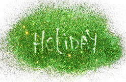 Word Holiday on green and golden glitter sparkles on white Stock Photography