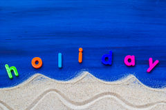 Word holiday laid sand blue board Stock Images