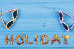 Word holiday made of amber stones and sunglasses on blue boards, summer time, copy space for text Royalty Free Stock Photography