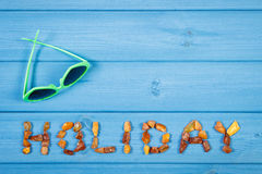 Word holiday made of amber stones and sunglasses on blue boards, summer time, copy space for text Royalty Free Stock Photos