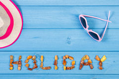 Word holiday made of amber stones, sunglasses and straw hat on blue boards, summer time, copy space for text Royalty Free Stock Photo