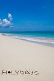 Word Holiday made of branches on white sand beach Stock Images