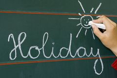 Word holiday and shine. Arm writing  chalky on table holiday and shine Stock Image