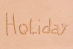 Word holiday in wet sand Royalty Free Stock Image