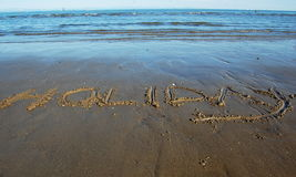 Word Holiday written in the sand. Word holiday written in the beach sand with sea view Royalty Free Stock Photo