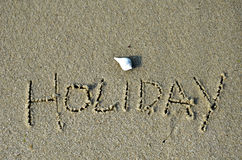 Word holiday written in the sand. Of a beach Royalty Free Stock Images