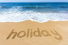 Word holiday written in sand on beach. Word holiday written at coast in sandy beach Stock Images