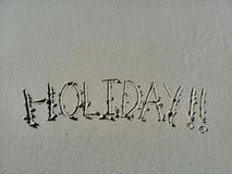 The word holiday written in the sand at the beach on shore. Holiday fun in the sun at the beach with words in the sand Royalty Free Stock Photo