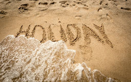 Word Holiday written on sand being washed off by sea wave Stock Photography