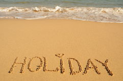The word holiday written on the shore. Holyday written on the shore Stock Photo