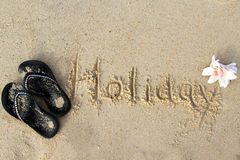 Word Holiday written on the wet sand. Decorated wit flip-flops and tropical flower Royalty Free Stock Photography