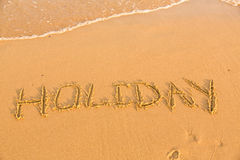 Word holiday on the yellow sandy beach Stock Image