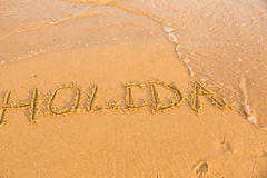 Word holiday on the yellow sandy beach Stock Photo
