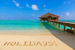 Word Holidays on beach. Nature holiday background Royalty Free Stock Photography