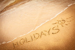 The word holidays written in the sand on a beach. Summer vacation concept. The word holidays written in the sand on beach Royalty Free Stock Images