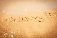 The word holidays written in the sand on a beach Stock Photo