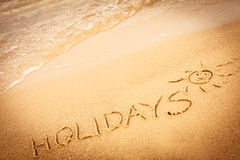 The word holidays written in the sand on a beach Royalty Free Stock Photos
