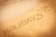 The word holidays written in the sand on a beach Royalty Free Stock Images