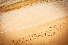 The word holidays written in the sand on a beach Stock Photos