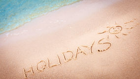 The word holidays written in the sand on a beach Royalty Free Stock Image