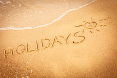 The word holidays written in the sand on a beach. Summer vacation concept. The word holidays written in the sand on beach Royalty Free Stock Photography