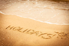 The word holidays written in the sand on a beach Stock Photography