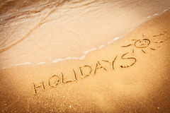 The word holidays written in the sand on a beach Royalty Free Stock Photo