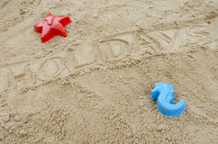 Word holidays written in sand. Word holiday written in sand. Concept of summer holidays Royalty Free Stock Photo