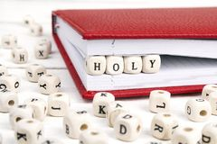Word Holy written in wooden blocks in notebook on white wooden t stock photo