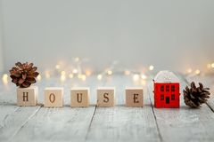 Word home on a cozy Christmas wooden house with a toy house. Cubes with the inscription House and a wooden model of a small multi-storey house on a Christmas royalty free stock images