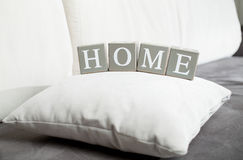 Word Home spelled on wooden blocks lying on sofa Royalty Free Stock Photo