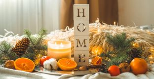 The word HOME and Tangerines in a winter composition, Christmas trees, candles, cones, cotton. Symbol of New Year and Christmas stock photos