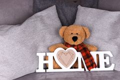 The word Home in white letters and teddy bear. On a sofa stock photos