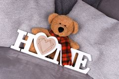 The word Home in white letters and teddy bear. On a sofa stock photography