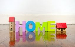 The word home with wooden letters on a wooden floor. With reflection Royalty Free Stock Photos