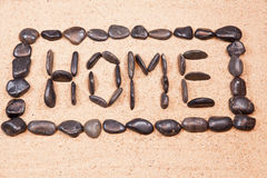 Word home written with pebbles on the sand Stock Images