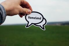 word homeland in hand on a white cloud in a field