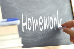 The word Homework hand written on a blackboard. Royalty Free Stock Image