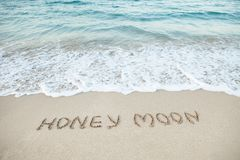 Word honeymoon written on beach Stock Image