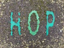 The word HOP on the floor in a kids park. The word HOP stencilled in turquoise and green onto the floor made out of wet pour rubber surface material in a kids stock photography
