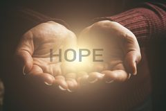 Word HOPE in abstract light in female hands, offering help, protection and support symbol. Sharing hope. Concept royalty free stock photo