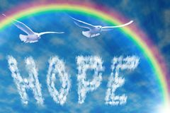 Word hope in the sky, under the rainbow. Royalty Free Stock Image