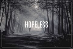 Word Hopeless. Road and sunbeams in strong fog in the forest. Royalty Free Stock Photos